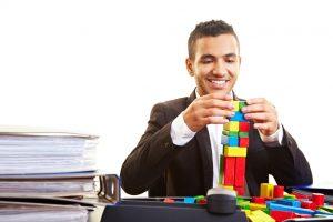 Junger Manager spielt am Schreibtisch mit bunten Bausteinen