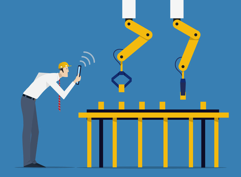 Industry 4.0 Factory Automation Concept. Robot hands controlled by skilled laborer with tablet PC.